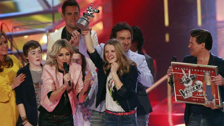 Winnares Laura (M) showt onder toeziend oog van presentatoren Wendy van Dijk en Martijn Krabbe haar award. De kandidaat van coach Marco Borsato won de finale van The Voice Kids, een talentenjacht voor zingende kinderen van RTL4. Beeld ANP Kippa