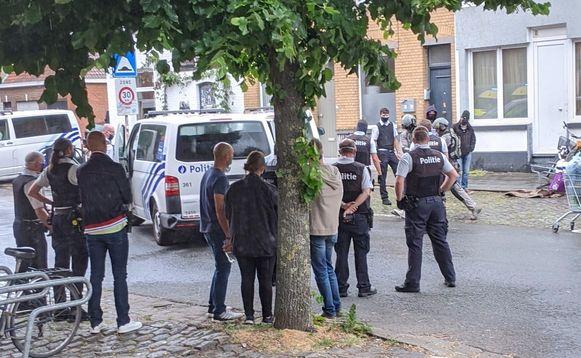 De gearresteerde man wordt (rechts op de foto), verscholen achter enkele politiemensen, weggeleid door agenten van de gespecialiseerde eenheden.