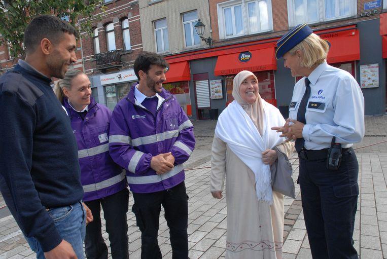 Een politieagente en stadswachters praten met een buurtbewoner.