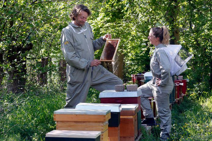 Imkers Wouter Hasekamp en Jessica van Beek bekijken een raam met honing uit een van de honingbijbroedkasten in Schoonrewoerd.