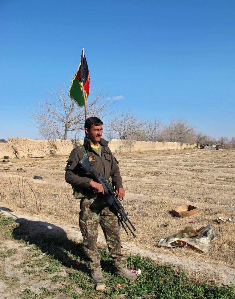 Een soldaat bij de Afghaanse vlag in de provincie Helmand. Beeld epa