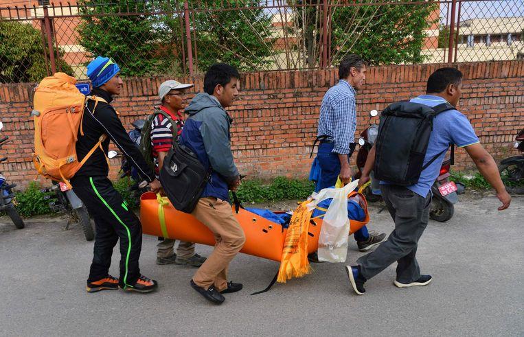Sherpa's en hulpdiensten brengen het lichaam van Ueli Steck naar een traumahelikopter. Beeld afp