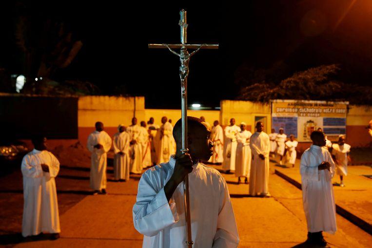 Een misdienaar met het kruis tijdens de kerstnachtdienst in de Notre Dame de Kinshasa in de Democratische Republiek Congo.