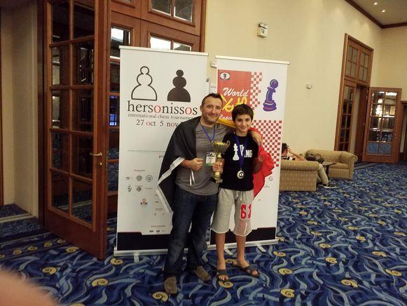 Daniel en papa Ben pronken in Chersonissos trots met de trofee van wereldkampioen snelschaken bij de -14-jarigen en met de Belgische driekleur.