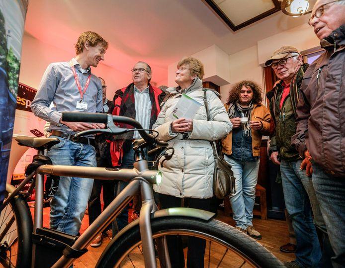 Bewoners van Loppersum maken kennis met een connected fiets. Een medewerker van Vodafone geeft uitleg.