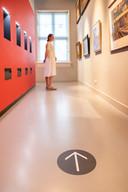 Een bezoeker bekijkt in alle ruimte de historische kunst van Museum Flehite.