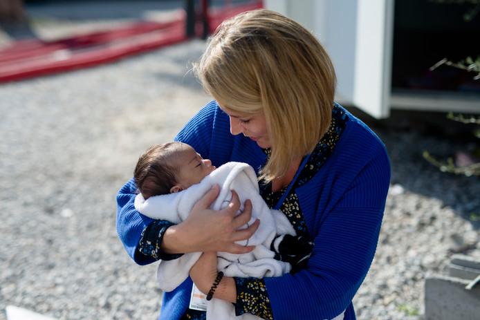 Brendy Boogaard met een jongetje van een maand oud. Ze heeft de moeder zojuist kleertjes voor het mannetje gegeven.