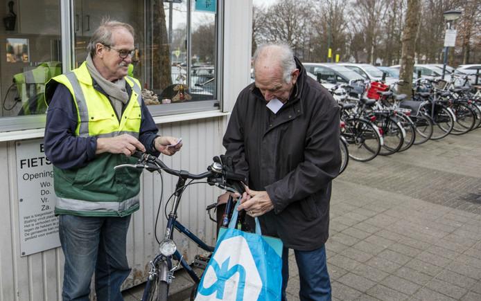 Jos Bunen met een klant bij de fietsenstalling.