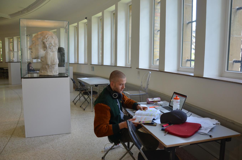 Rechtenstudent Felix Blommaert studeert met een beeld van Rodin aan zijn zijde.