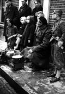 Een Engelse soldaat warmt, omringd door enkele inwoners van Oldenzaal, z'n eten op.