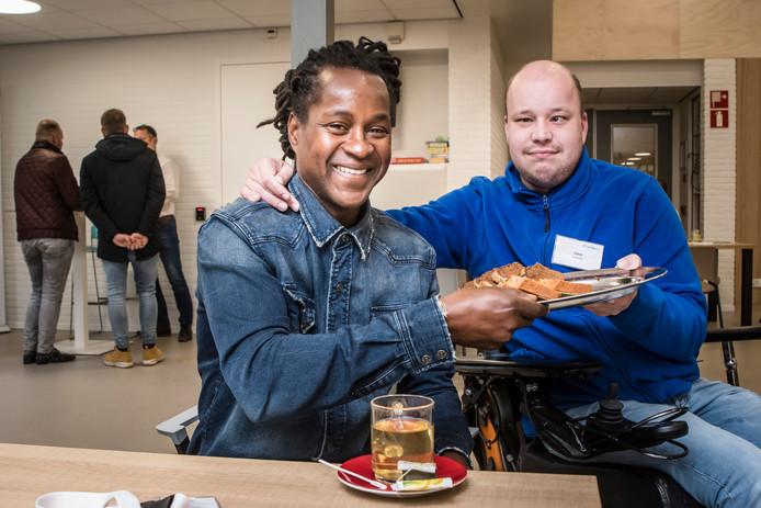 Bewoner Dylan van 't Bouwhuis biedt Timotéo Afonso, bezoeker van de wervingsdag nieuwe woonbegeleiders, een kop thee en een plak cake aan. Op de achtergrond wordt een kennismakingsgesprek gevoerd.