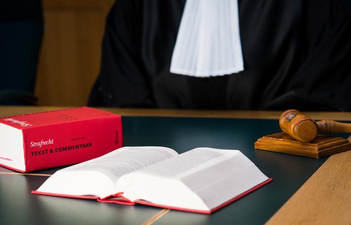 Een rechter met wetboek in de rechtzaal.