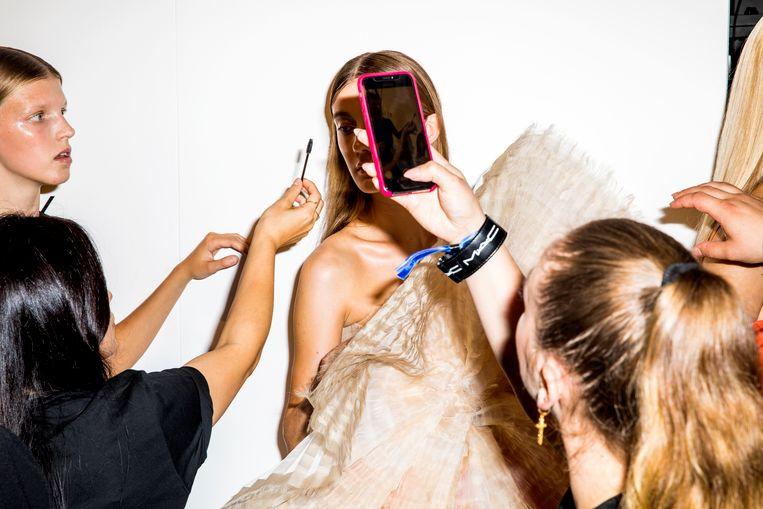 Een model wordt opgemaakt voor de Amsterdam Fashion Week. Beeld Marie Wanders