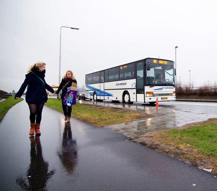 Uitstappende passagiers bij de bushalte aan de Van Heemstraweg ter hoogte van de Nieuwstraat in Dreumel.