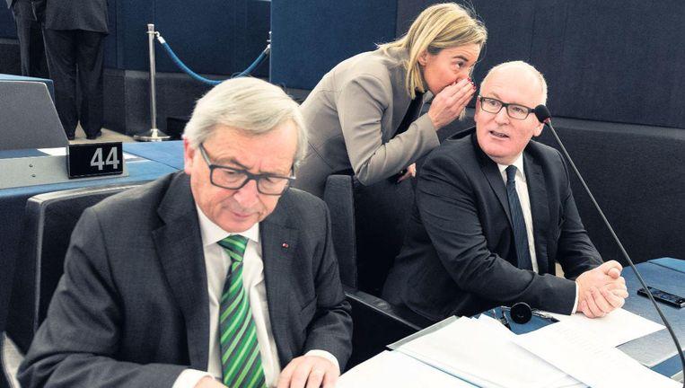 In de bankjes van het Europees Parlement in Straatsburg: een onderonsje tussen Federica Mogherini en Frans Timmermans. Links: Jean-Claude Juncker Beeld epa