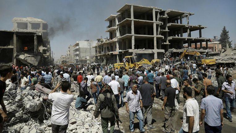 Syriërs verzamelen zich op de plaats waar één van de bomaanslagen plaatsvond. Beeld AFP