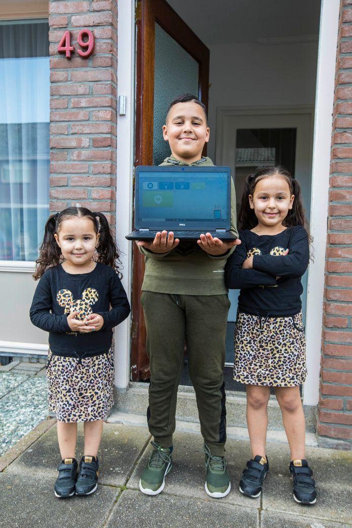 Nihad, Rayan en Noor (vlnr), kinderen van Halima Dib, zijn dolblij met de laptop die zij geleend hebben van Stichting Leergeld. De oude ging plotseling kapot en geld voor een nieuwe was er niet. Foto: Nico Schouten