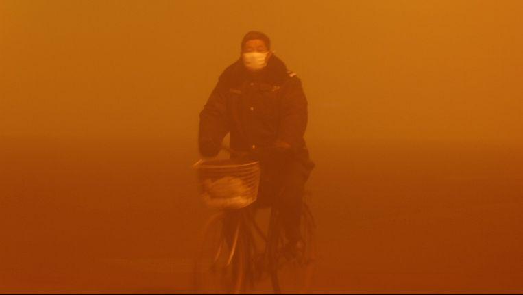 Een man rijdt door een zwaar vervuilde regio in het oosten van China. Beeld null