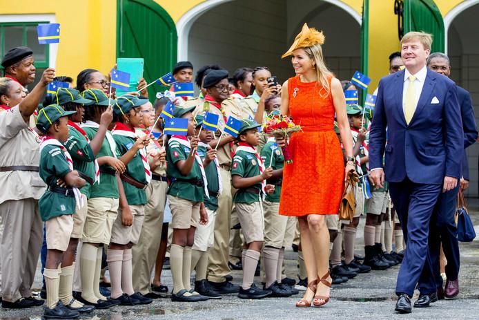 Enthousiaste kinderen en volwassenen begroeten het koningspaar op Curaçao.