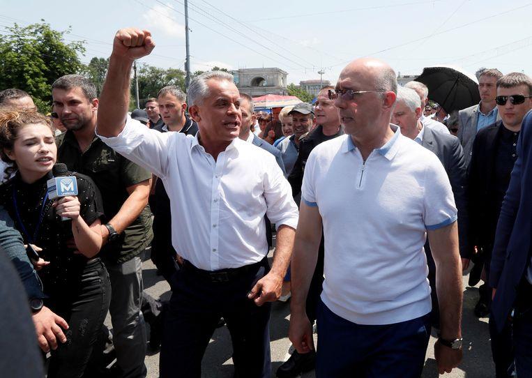 De Moldavische interim president Pavel Filip (r) en leider van de Democratische Partij (DP) Vladimir Plahotniuc (l) nemen deel aan een demonstratie in Chisinau Beeld REUTERS/Valentyn Ogirenko