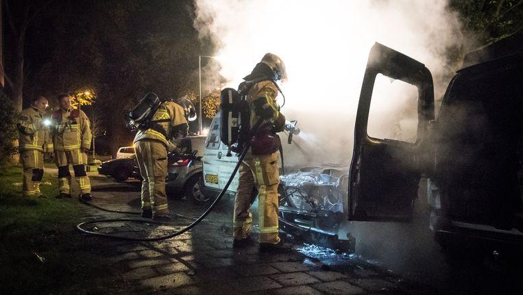 De politie blust een autobrand op de Molenaarsweg in Noord in april 2015. De brand in de grijze Landrover is vermoedelijk aangestoken. Beeld Rowin Ubink