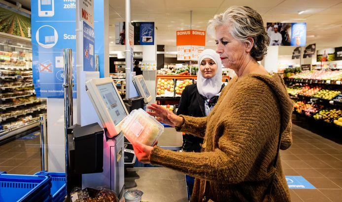 Klanten gebruiken de zelfscanner in een filiaal van Albert Heijn. De supermarktketen komt binnenkort met een systeem zónder betaalmoment in de winkel. Klanten betalen dan achteraf met automatische incasso.