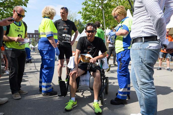 Neurochirurg Kuan Kho komt op adem in een rolstoel na de finish nadat hij met een pruik vol elektroden de marathon heeft volbracht.