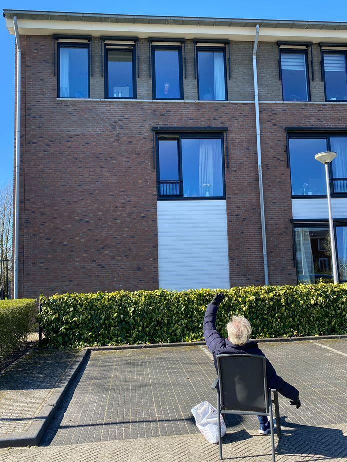 De jongste zus van mevrouw Bloemendaal zwaait naar haar zus, die achter het derde raam van links staat.