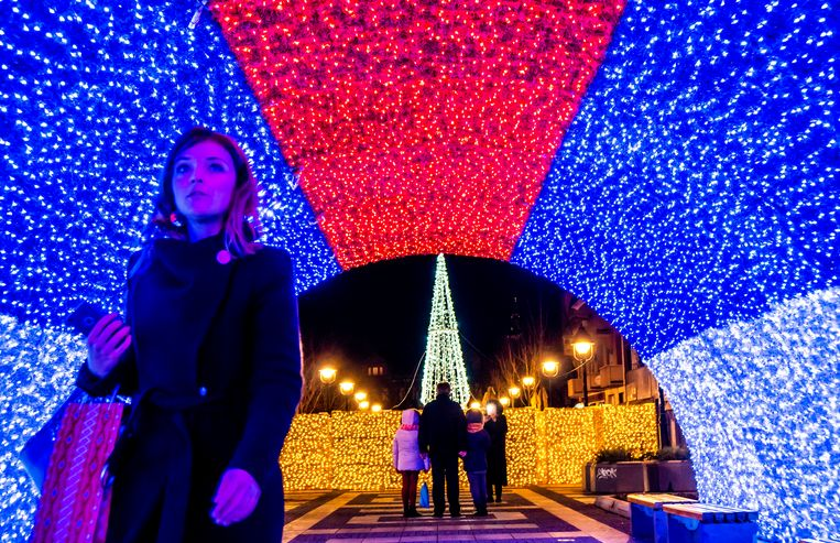 Een vrouw loopt in de de Servische hoofdstad Belgrado door een lichttunnel in de kleuren van de nationale vlag.