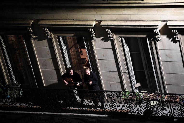 Twee vrouwen in Marseille brengen een ode aan de zorg vanaf hun balkon. Beeld AFP