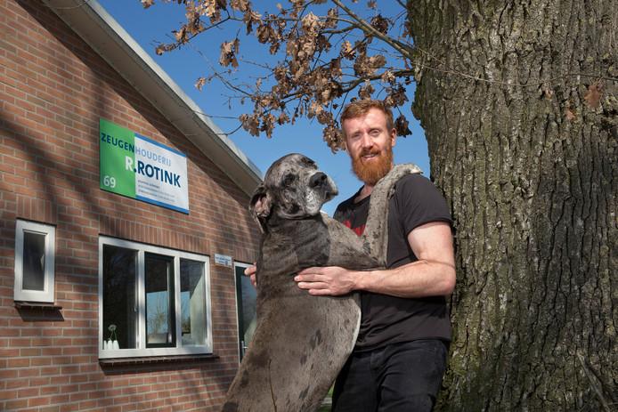 Rik Rotink met hond Bowie bij de ingang van de zeugenhouderij. Foto Theo Kock