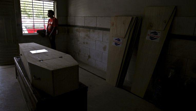 Een vrijwilliger wacht bij de kist van een van de 150 dodelijke slachtoffers van de extreme hitte in Karachi.