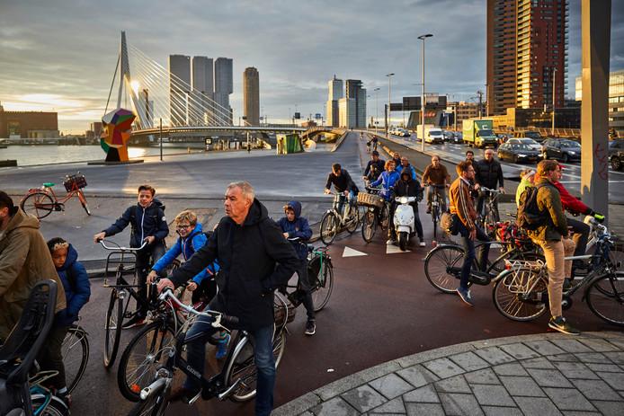 Scholieren en forenzen fietsen van Zuid naar Noord over de Erasmusbrug in Rotterdam.