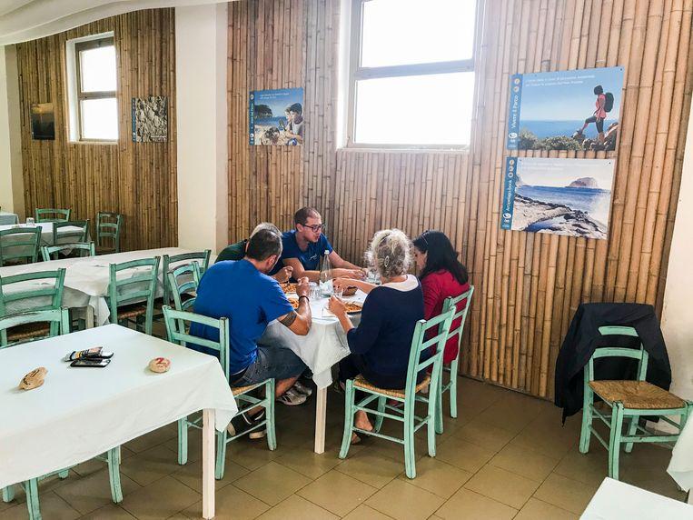 De drie gedetineerden wiens werk het nu is te koken voor toeristen, lunchen zelf voor ze weer teruggaan naar hun cellencomplex. Beeld null