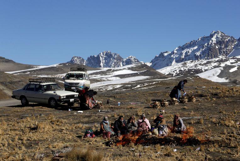 Een aantal Aymara, een oorspronkelijke bevolkingsgroep in Bolivia, is bij elkaar gekomen om Pachamama, Moeder Aarde, te vereren. Die ceremonie begint traditiegetrouw op 1 augustus. Beeld REUTERS