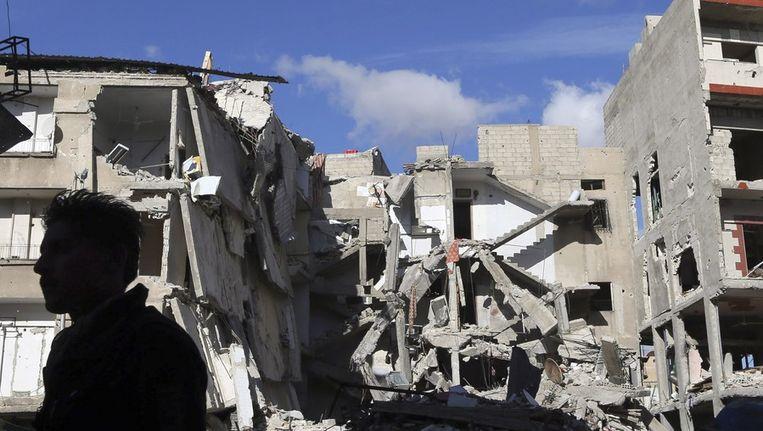 Een man staat voor een gebouw in Damascus dat is vernietigd na een luchtaanval van het Syrische leger. Beeld reuters
