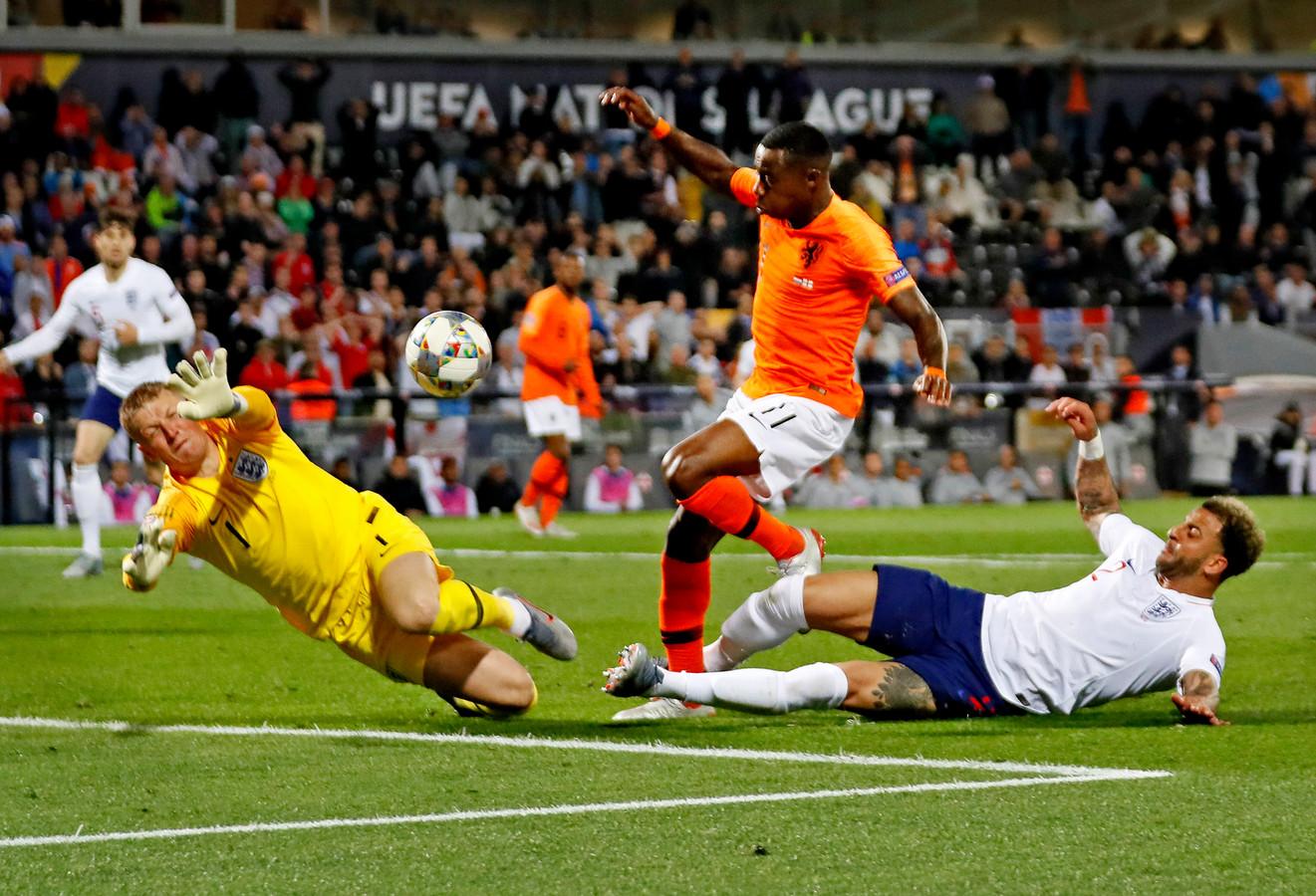 Kyle Walker raakt als ;laatste de bal bij de 2-1 van Oranje. Midden: Quincy Promes. Links Jordan Pickford.