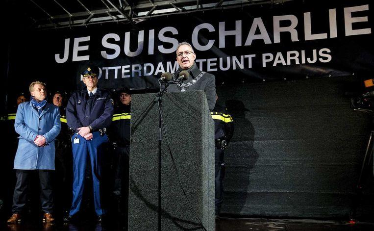 (VLNR) Hoofdredacteur Christiaan Ruesink van het Algemeen Dagblad, korpschef Frank Pauw en burgemeester Ahmed Aboutaleb houden een minuut stilte tijdens een demonstratie naar aanleiding van de aanslag in Parijs. Beeld anp