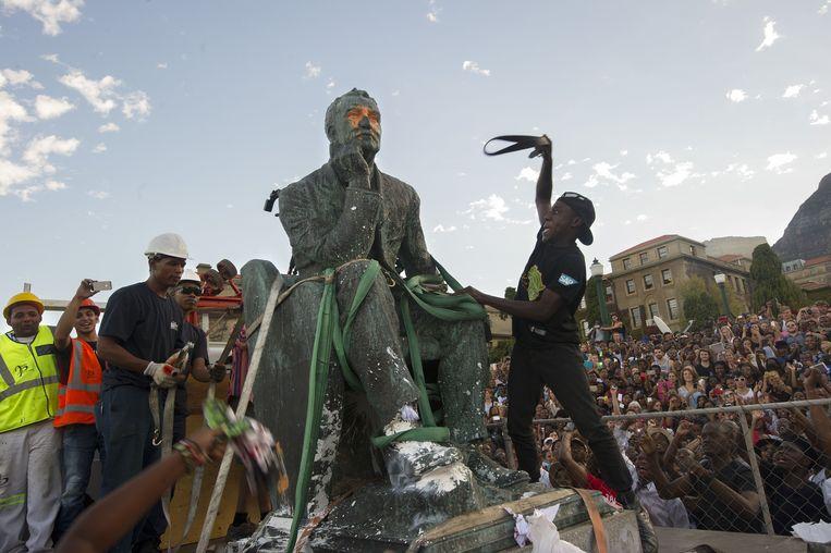 Tijdens de studentenprotesten moesten beelden van koloniale leiders het ontgelden. Boven: Louis Botha in Kaapstad, onder Cecil Rhodes in het Nationaal Park en boven de ontmanteling van Cecil Rhodes op de universiteitscampus. Beeld AFP