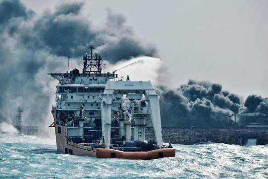 Blusboten proberen de vuurzee aan boord van de Sanchi  te bedwingen.