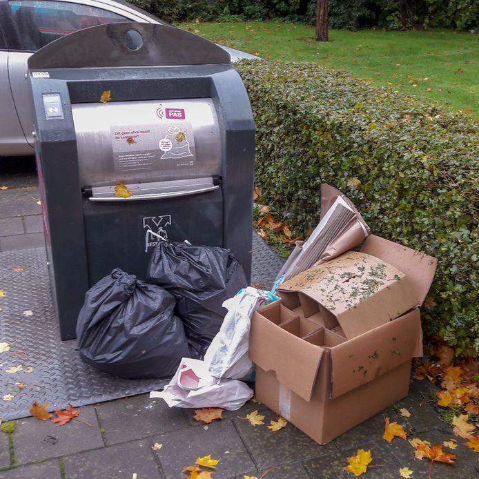 Afval naast een ondergrondse afvalcontainer in Arnhem-Zuid die uitsluitend met een afvalpas te openen is.