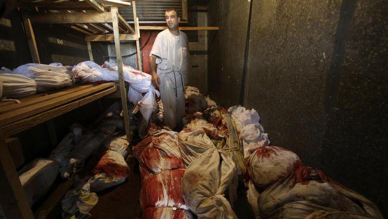 Een Palestijn tussen de lichamen in een koelcel in Rafah. Beeld reuters