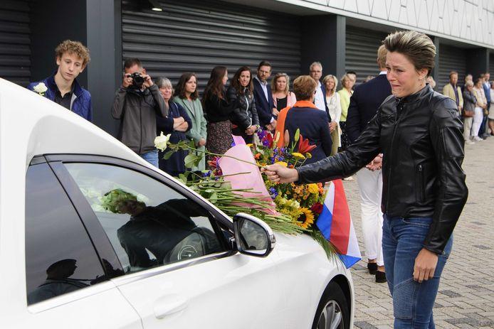 Jorien ter Mors legt een roos op de rouwauto.