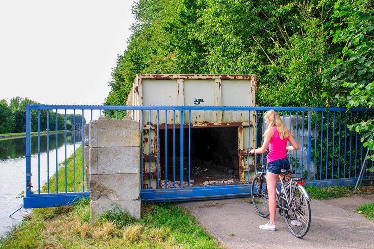 Een containermuur moet sinds enkele jaren fietsers en wandelaars de doorgang langs het jaagpad beletten.