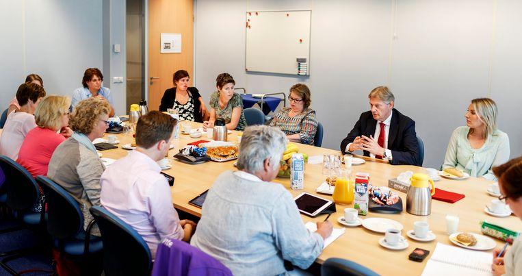 Wijkverpleegkundigen rond de tafel met staatssecretaris Martin van Rijn tijdens een bezoek in 2016. Beeld ANP