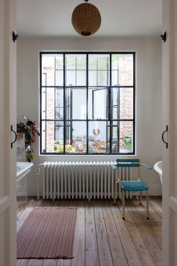 De badkamer is artisanaal afgewerkt met een houten vloer, ijzeren ramen en een gietijzeren verwarming.