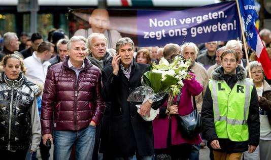 Broer Simon Fortuyn (met telefoon) en de chauffeur van Pim Fortuyn Hans Smolders (paars jack) tijdens de demonstratie tegen de strafkorting van Volkert van der G.