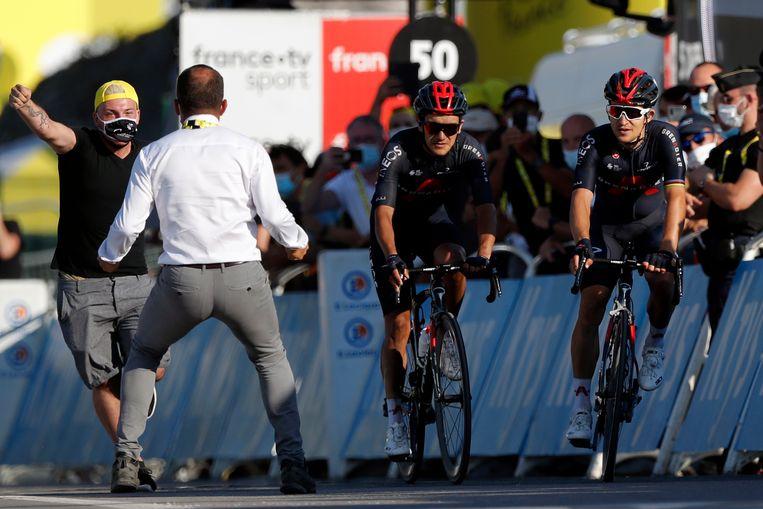 Een medewerker van de Tour haalt een fan van het parcours als de Poolse wielrenner Michal Kwiatkowski (rechts) richting de finish fietst om de etappe te winnen.  Beeld AP
