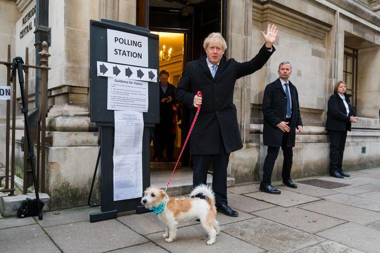 De Britse premier Boris Johnson bracht zijn stem uit in gezelschap van zijn hond Dylan. De eerste exitpolls wijzen op een ruime verkiezingszege voor de Conservatieven. Beeld EPA