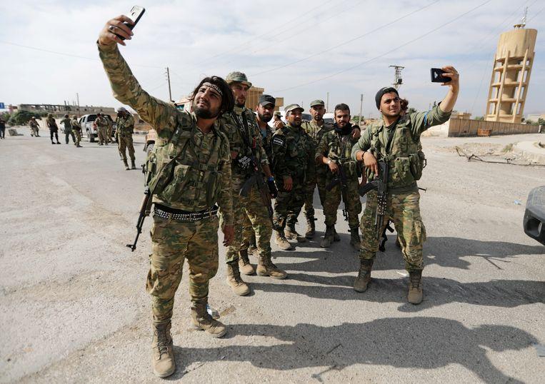 Door Turkije gesteunde Syrische rebellen nemen selfies bij grensplaats Tel Abyad op 14 oktober 2019.